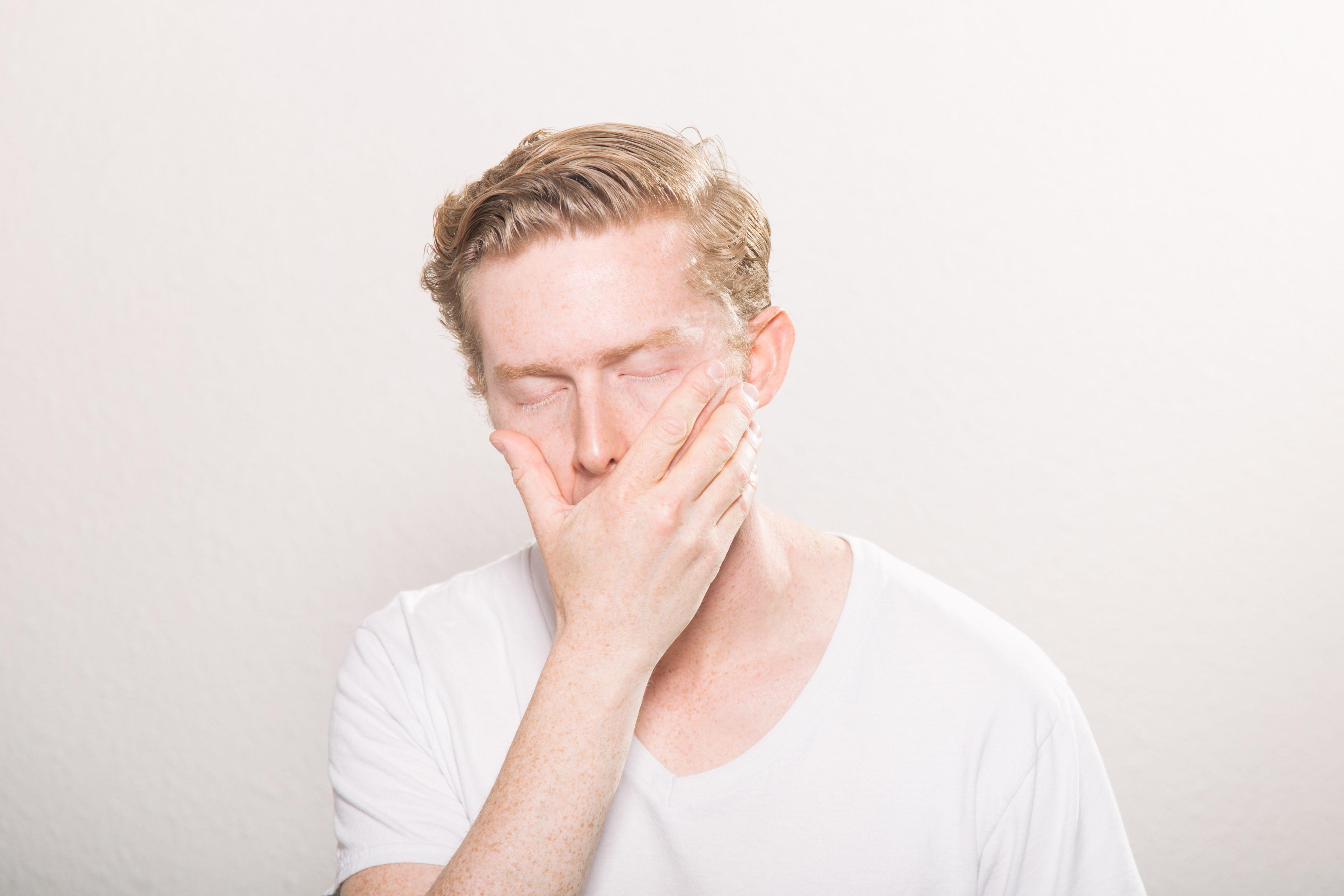口を抑える男性